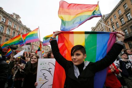 Gay rights activists march with flags and placards during a May Day rally in St. Petersburg